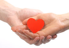 Valentine's heart in human hands. Two hands (female and male) holding red Valentine's heart Stock Photo