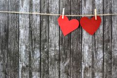 Valentine`s hearts on a dark wooden background. Felt red and coral Valentine`s hearts on a dark wooden background. Festive concept stock photos