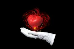Valentine's magic. Illusionist in white glove keeps heart on a palm Stock Images