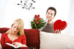 Valentine's: Man Sneaks Up with Valentine Gifts For Girlfriend. Series with Caucasian men and women celebrating the Valentine's holiday with a romantic dinner Royalty Free Stock Photography