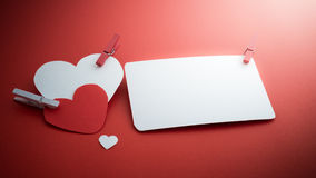 Valentine's paper hearts with a blank business card and Clothesp Stock Photography