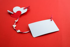 Valentine's paper hearts with a blank business card and Clothesp Royalty Free Stock Image