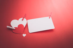 Valentine's paper hearts with a blank business card and Clothesp Royalty Free Stock Images