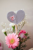 Valentine's Party Heart Centerpiece. A bouquet of flowers with a felt fabric heart centerpiece DIY project for a love themed party Royalty Free Stock Photography