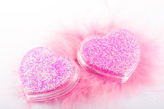 Valentine?s pink hearts. Two shiny hearts on pink feather Stock Image