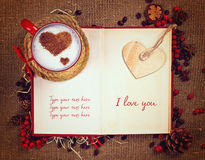 Valentine`s postcard. Cup of coffee on open book with wooden heart on it. Royalty Free Stock Photography