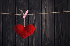Valentine`s Red heart on rope on wooden background Stock Photography