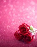 Valentine's Rose. Three red roses over pink glittering background Stock Photography