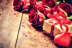 Valentine's setting with bouquet of red roses and present Royalty Free Stock Image