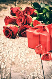 Valentine's setting with bouquet of red roses and present Royalty Free Stock Photo