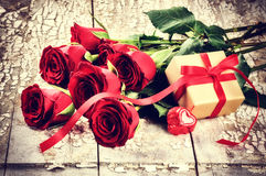 Valentine's setting with bouquet of red roses and present in box Royalty Free Stock Photos