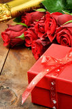 Valentine's setting with red roses, champagne and gift box Stock Photo