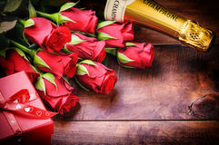 Valentine's setting with red roses, champagne and gift stock photo