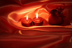 Valentine`s still life. Valentine`s card with couple of candles on satin background royalty free stock photos