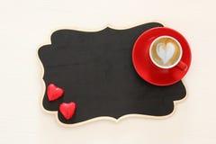 Valentine& x27; s-Tageshintergrund roter Tasse Kaffee mit Herzformschaum und -schokolade Draufsichtbild stockbilder