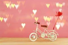 Valentine& x27; s-Tagesromantischer Hintergrund mit weißem Weinlesefahrradspielzeug und Herz auf ihm über Holztisch lizenzfreies stockfoto
