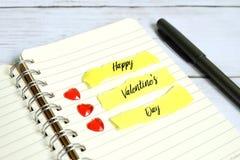 Valentine' s-Tagesthema Ein kleines rotes Herz auf einem Buch geschrieben mit ' GLÜCKLICHES VALENTINE' S DAY' lizenzfreie stockbilder