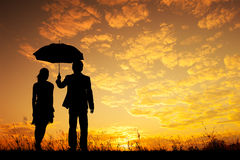 Valentine silhouette of Man and woman holding umbrella in evening sunset Stock Photos