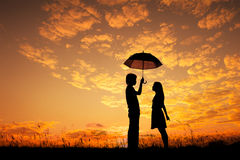 Valentine silhouette of Man and woman holding umbrella in evening sunset Stock Image
