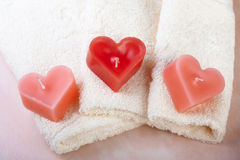 Valentine spa. Heart shaped candles on white towel Royalty Free Stock Image