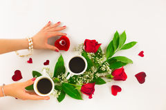 Valentine still life with pearl ring in man hand, red roses and woman hand with coffee. Marriage proposal with pearl ring in man hand, red roses and woman hand Stock Photos