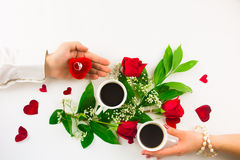 Valentine still life with pearl ring in man hand, red roses and woman hand with coffee. Marriage proposal with pearl ring in man hand, red roses and woman hand Royalty Free Stock Photo