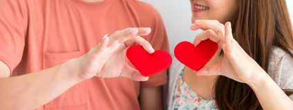 Valentine and Sweetest day, red heart on couple hands. In love stock images