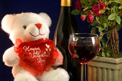 Valentine teddy bear and wine. A view of a cute white Valentine teddy bear, ready to celebrate the holiday with a bottle of wine, a wine goblet and miniature royalty free stock photo