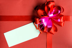 Valentine theme. Blank white tag on red gift box with ribbon flower Royalty Free Stock Photo