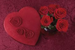 Valentine Themed Background With Heart-shaped Chocolate Box and Red Rose Bouquet on Red Crushed Velvet Background. Valentine themed background with red leather Royalty Free Stock Photography