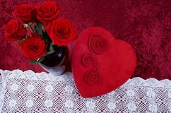 Valentine Themed Background With Heart-shaped Chocolate Box and Red Rose Bouquet on Red Crushed Velvet Background. Valentine themed background with red leather Stock Photography
