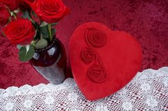 Valentine Themed Background With Heart-shaped Chocolate Box and Red Rose Bouquet on Red Crushed Velvet Background. Valentine themed background with red leather Stock Photo