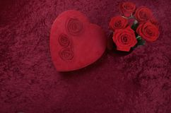 Valentine Themed Background With Heart-shaped Chocolate Box and Red Rose Bouquet on Red Crushed Velvet Background. Valentine themed background with red leather Royalty Free Stock Image