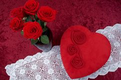 Valentine Themed Background With Heart-shaped Chocolate Box and Red Rose Bouquet on Red Crushed Velvet Background. Valentine themed background with red leather Stock Images