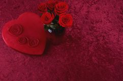 Valentine Themed Background With Heart-shaped Chocolate Box and Red Rose Bouquet on Red Crushed Velvet Background. Valentine themed background with red leather Stock Photos