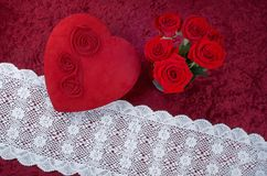 Valentine Themed Background With Heart-shaped Chocolate Box and Red Rose Bouquet on Red Crushed Velvet Background. Valentine themed background with red leather Royalty Free Stock Photo