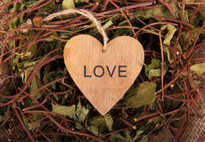 Valentine from a tree with an inscription. Wooden valentines on background of dried twigs. Decoration made from natural materials. Stock Photos