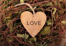 Valentine van een boom met een inschrijving Houten valentijnskaarten op achtergrond van droge takjes Decoratie van natuurlijke ma Stock Foto's