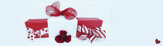 Valentine web banner 2. Red and white wrapped packages with red roses on a white background and one red heart.  There is room for your text on the left and right Royalty Free Stock Photos