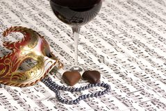 Valentine wine with music. A glass of red wine with a black pearl necklace and two chocolates. Sharing wine with a unknow lover Royalty Free Stock Photography