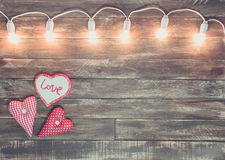 Valentine wooden textured background with light garland Stock Images