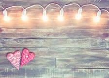 Valentine wooden textured background with light garland Stock Photos