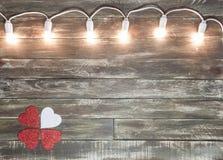 Valentine wooden textured background with light garland Stock Photo