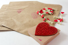 Valentine wrapper. Present wrapper with craft paper envelope, small clothepins and cute heart stamp on the white background Stock Photography