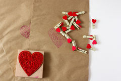 Valentine wrapper. Present wrapper with craft paper envelope, small clothepins and cute heart stamp on the white background Royalty Free Stock Image
