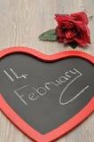 Valentine& x27; día de s Un tablero del negro de la forma del corazón con el 14 de febrero Imágenes de archivo libres de regalías