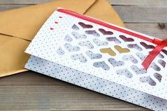 Valentine& x27; dia de s cartão branco com os corações cortados e envelope dourado na tabela de madeira, exposição do produto Foto de Stock