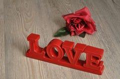 Valentine& x27 ; jour de s Aimez dans les lettres rouges avec une rose rouge Images stock