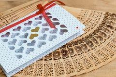 Valentine& x27 ; jour de s carte blanche avec les coeurs coupés et enveloppe d'or sur la table, affichage de produit Ventilateur  Photo libre de droits