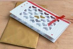 Valentine& x27 ; jour de s carte blanche avec les coeurs coupés et enveloppe d'or sur la table en bois, affichage de produit Photographie stock libre de droits